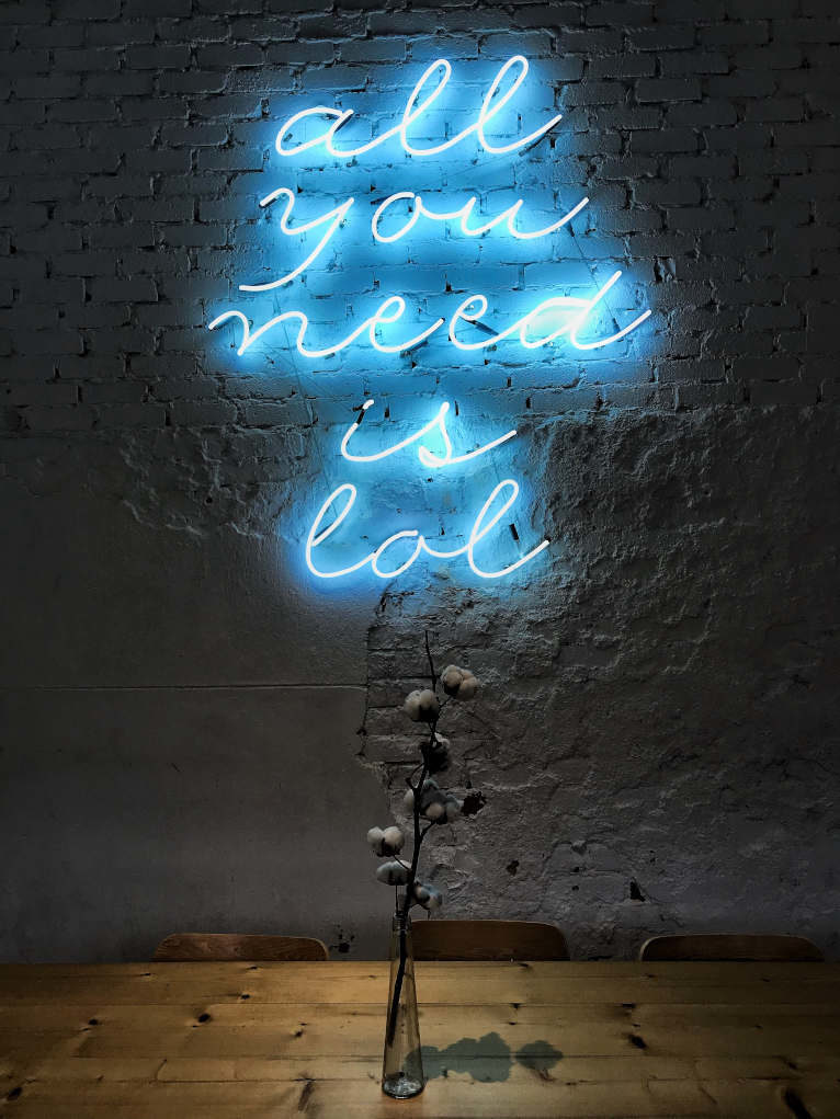 "Lit up in blue neon are the words ""all you need is lol""."