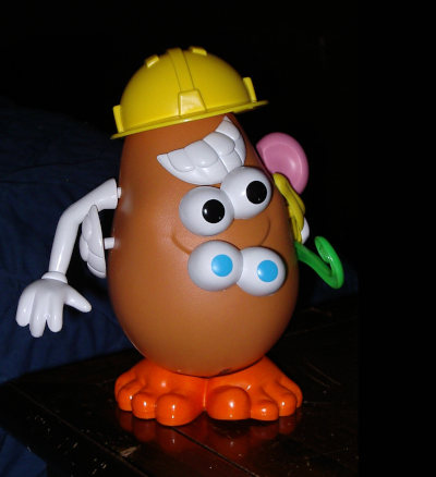 A Potato Head toy put together in a mixed-up way, with four eyes, two sets of teeth and other unusual choices.